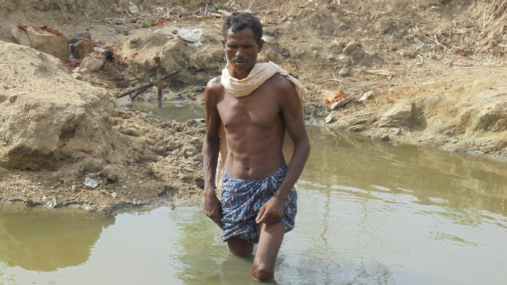 A community member mapping the water level in the small pond in Kundei Jharana Village